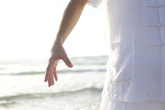 homme en blanc le bras le long du corps pour contacter son champs énergétique